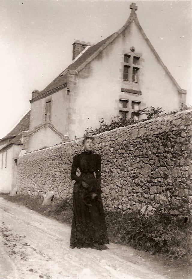 Dame devant mur en pierre de maison