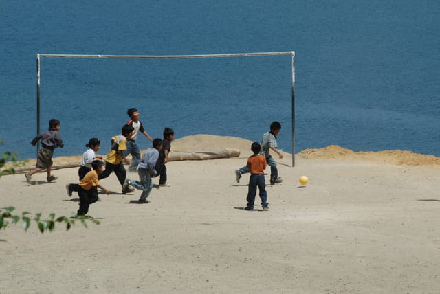 Enfants jouant au foot au bord du lac Atitlan
