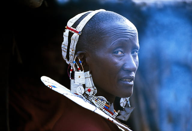 Femme masaï devant sa case enfumée