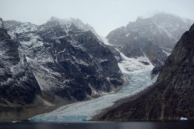 Glacier tombant dans la mer. La brume noie le sommet des montagnes.