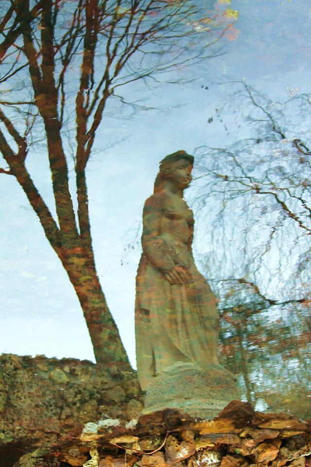 Reflets d'une statue dans un jardin public