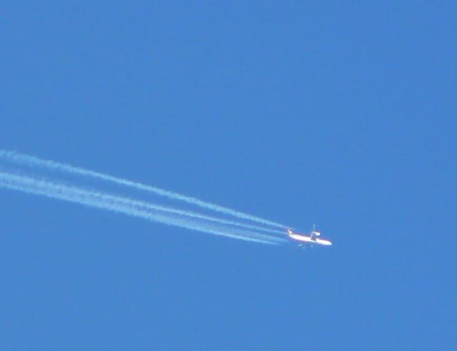 Très haut dans le ciel, un avion passe