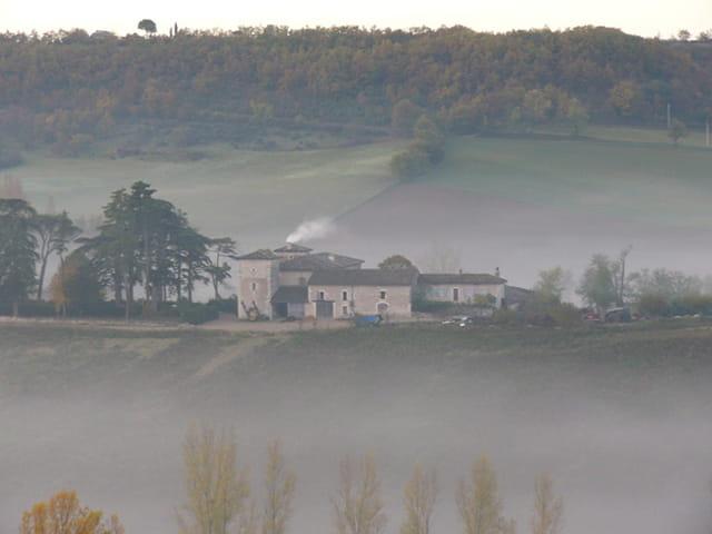 Une ferme dans la brume